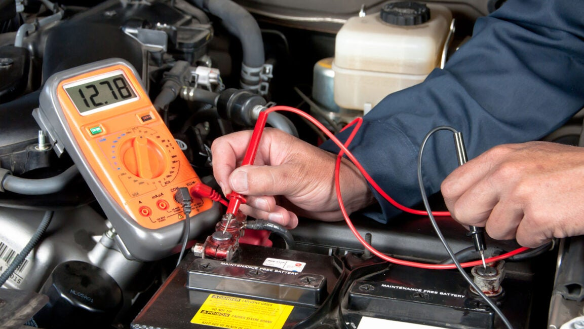 A mechanic holds a multimeter to test a battery.