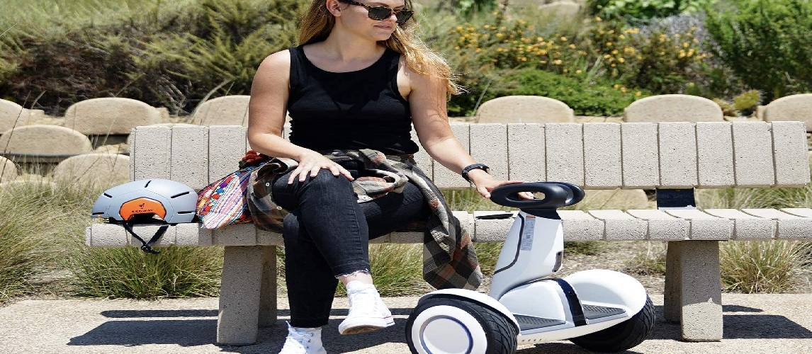 Girl is taking a rest on the bench from the riding a Segways scooter