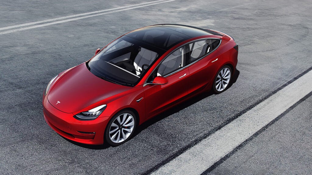 A red Tesla Model 3 on black pavement.