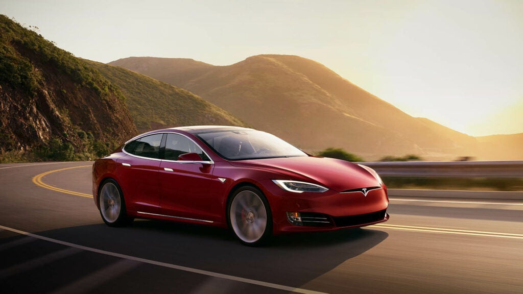 A red Tesla Model S drives down a winding road.
