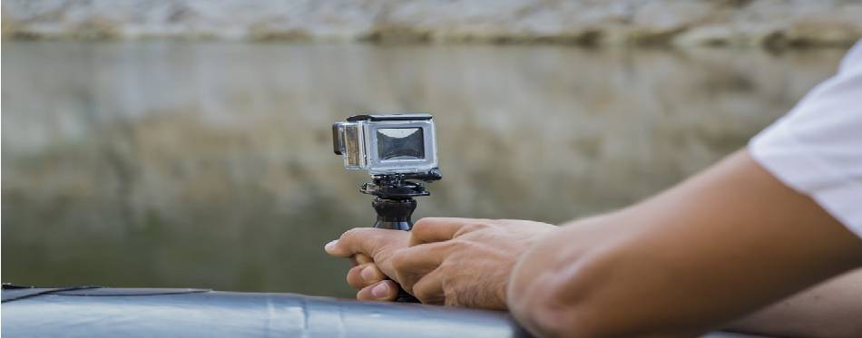 Hand holding small action camera with waterproof case