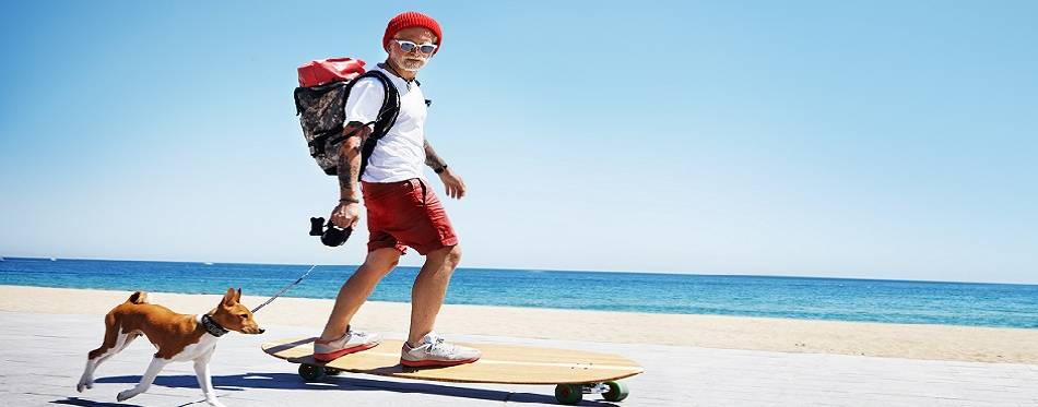 A man is walking his dog while riding skateboard on the beach