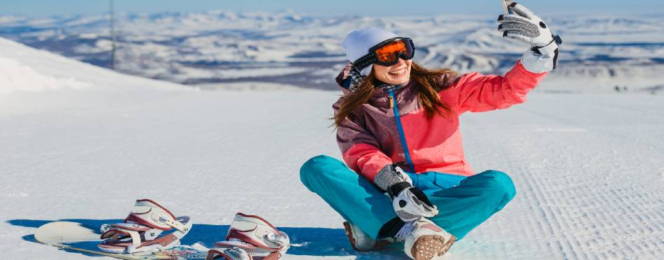 Cheerful snowboarding girl sitting and taking selfies in the mountains