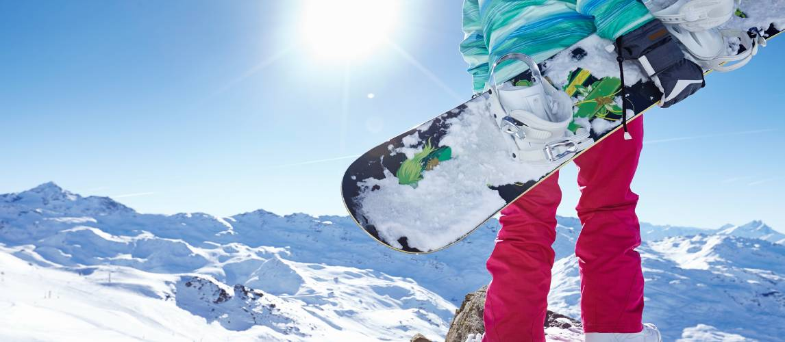 Young woman with snowboard standing in the mountains