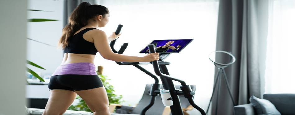 Woman Training On Elliptical Trainer At Home