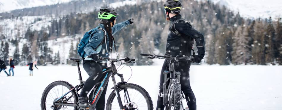 Two mountain bikers resting outdoors in winter