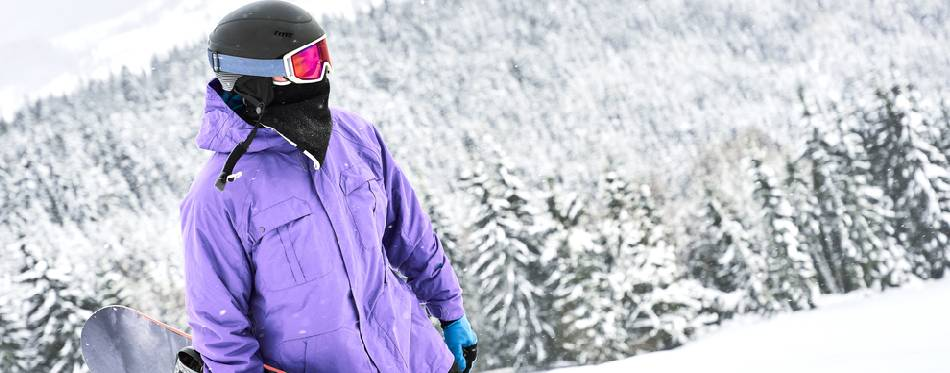 Woman is standing at the snow wearing balaclava