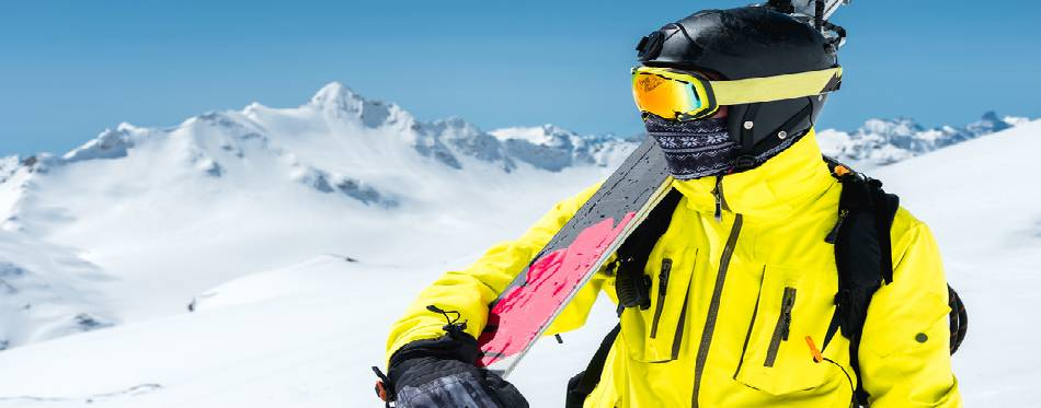 Snowboarder standing at the snow and holding snowboard