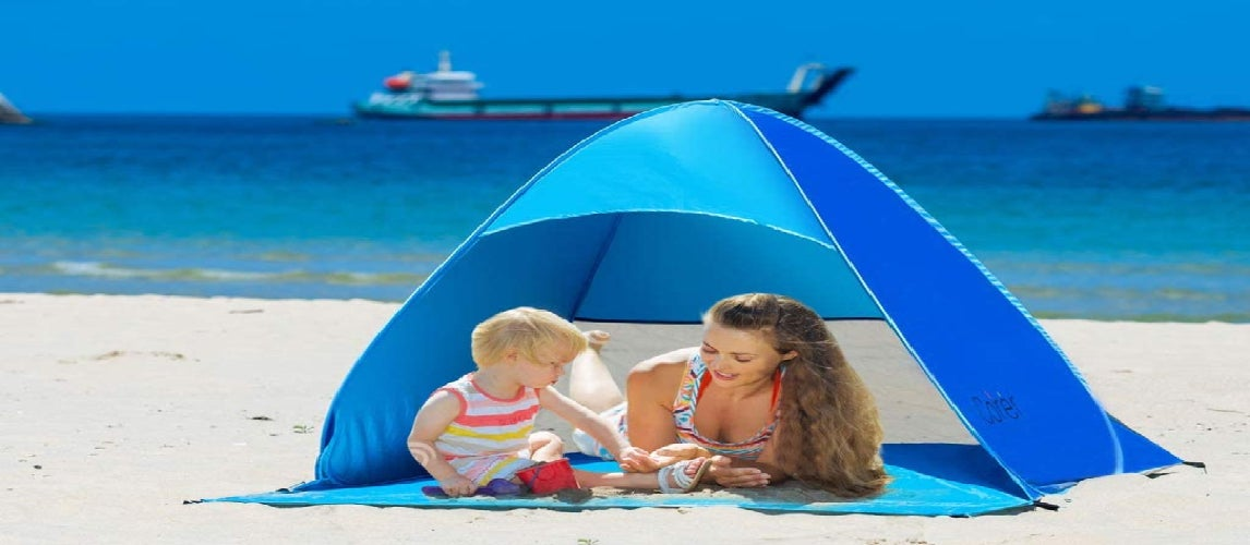 Mom and son relaxing on the beach under beach shade