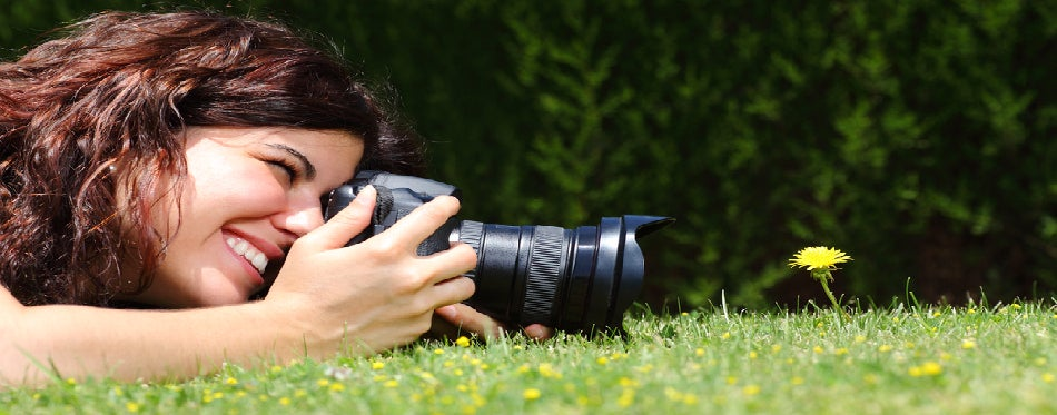 Woman taking a photography of the flower on the grass