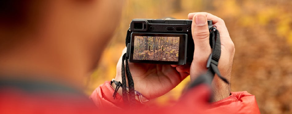Young man taking pictures with a compact camera through the forest in the fall