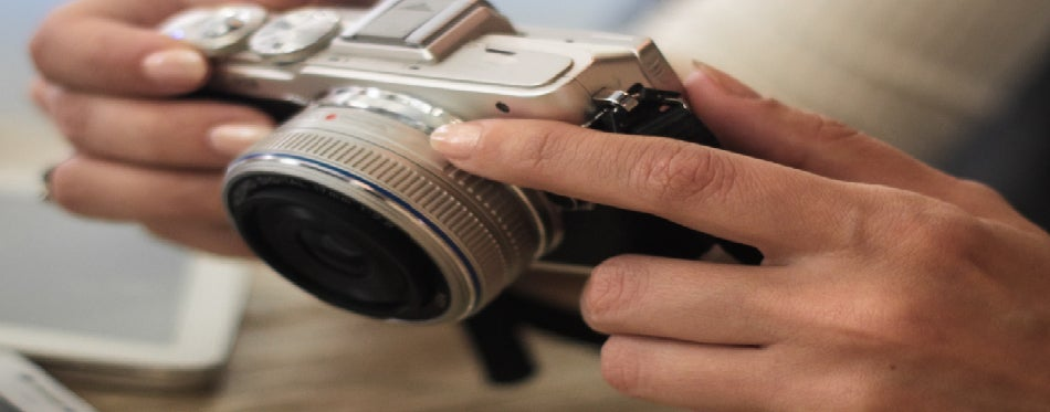 Woman holds a compact photo camera