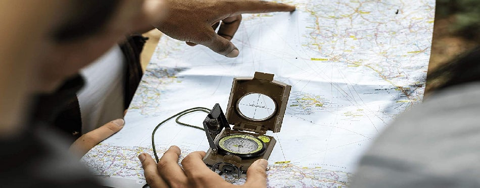 Two hands searching location on the map using a compass