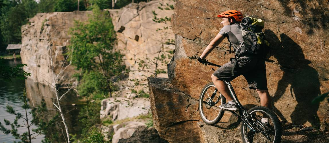 Young trial biker with bicycle standing on cliff