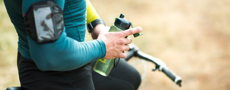 Cyclist holding bottle of water