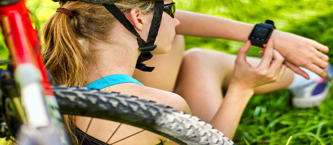 Cyclist girl is sitting on the grass and looking in her cycling watch