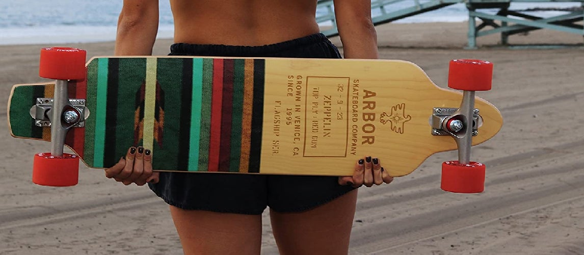 A girl standing on the beach and holding her longboard
