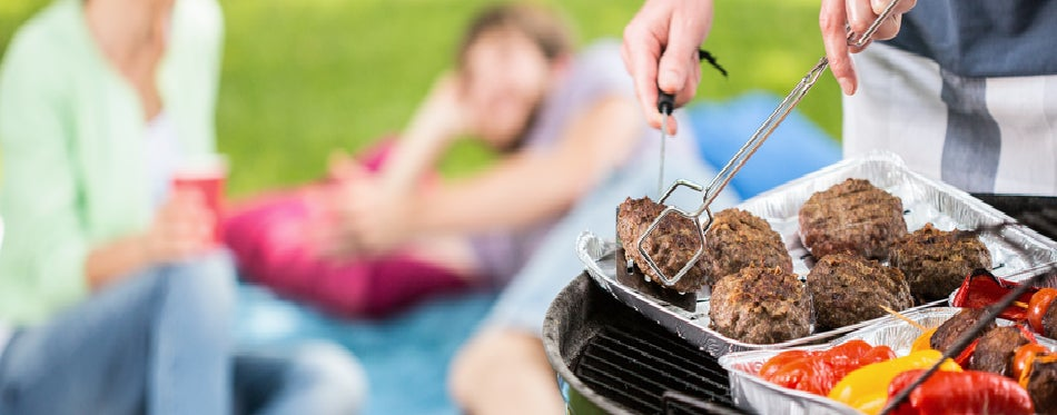 Man grilling meat and vegetables
