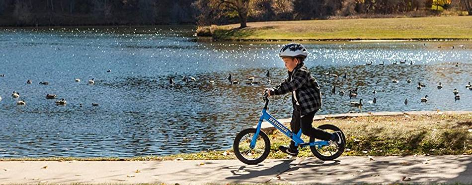Little boy is riding a balance bike on the lake shore