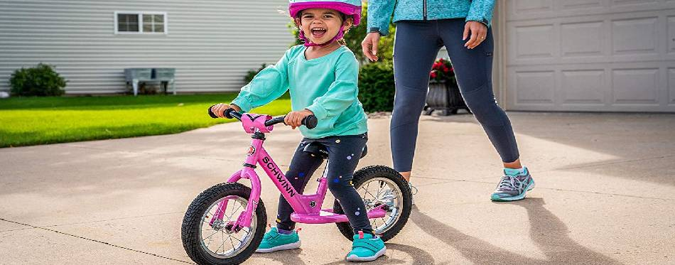 Litlle girl is happy with her balance bike
