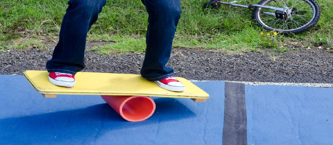 A boy is standing on the balance board