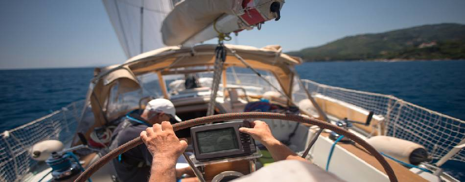 Sailor holding the helm of the sailboat
