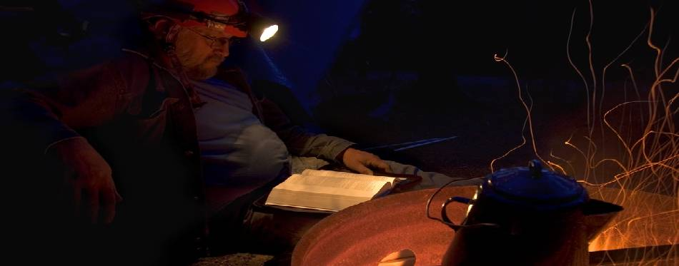 Man Reading Bible At Night Next To Fire