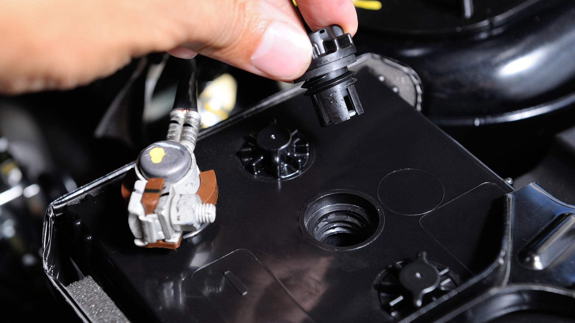 Opening the cap of a car battery to recondition it.