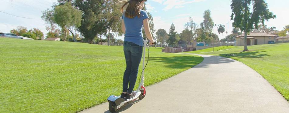 A girl drives an electric scooter around the block