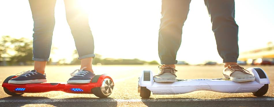 Young man and woman riding on the Hoverboard in the park