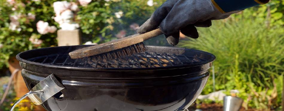 Male hand with gloves cleans a grill.