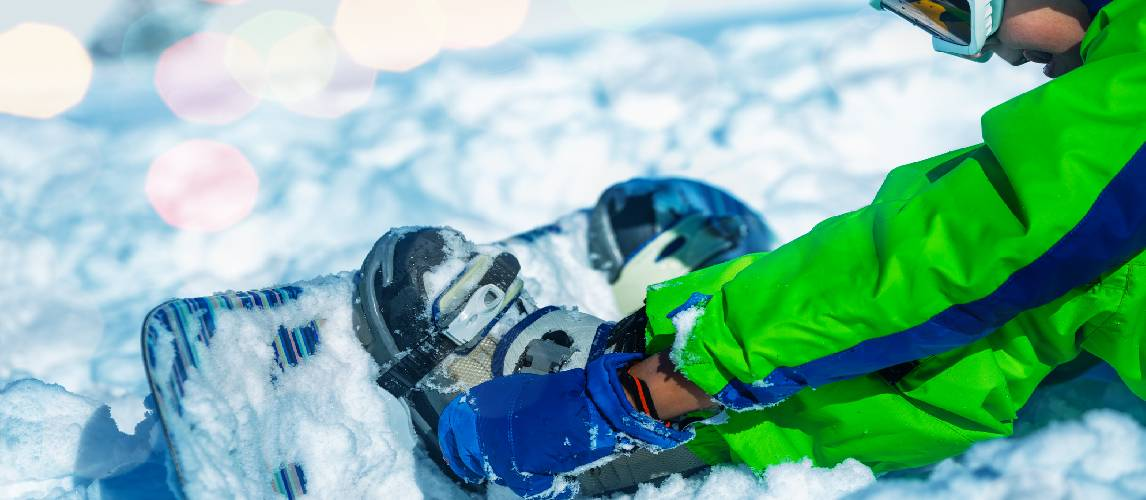Close up of a boy attach snowboard to the legs sitting in snow