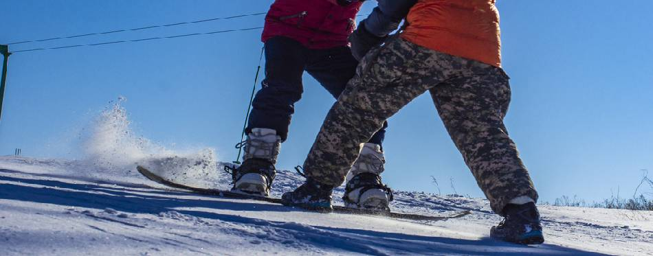 Children learn to snowboard on the mountainside
