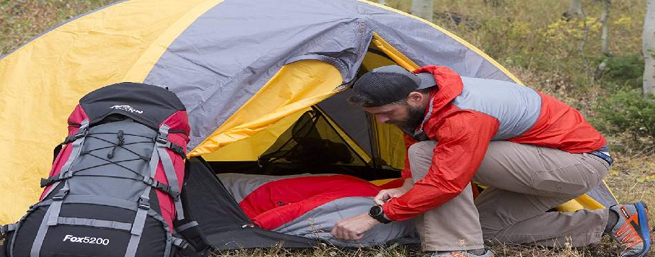 The camper is packing his sleeping bag