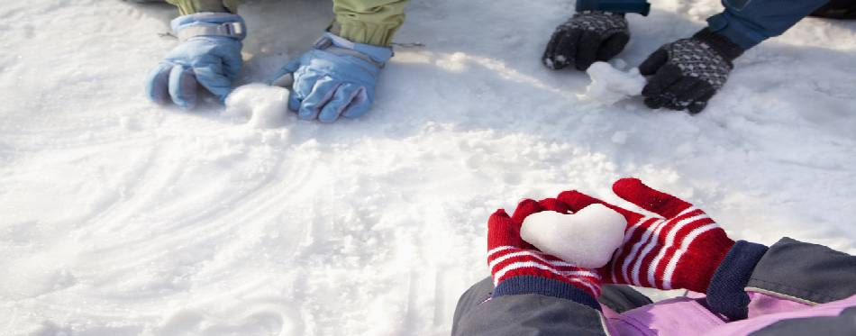 Hands in Winter Gloves Playing in the Snow