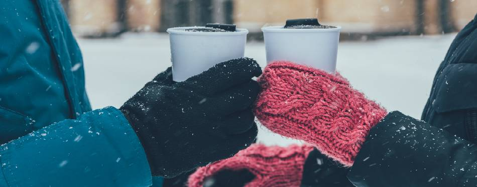 couple with hot drinks holding hands on street in winter