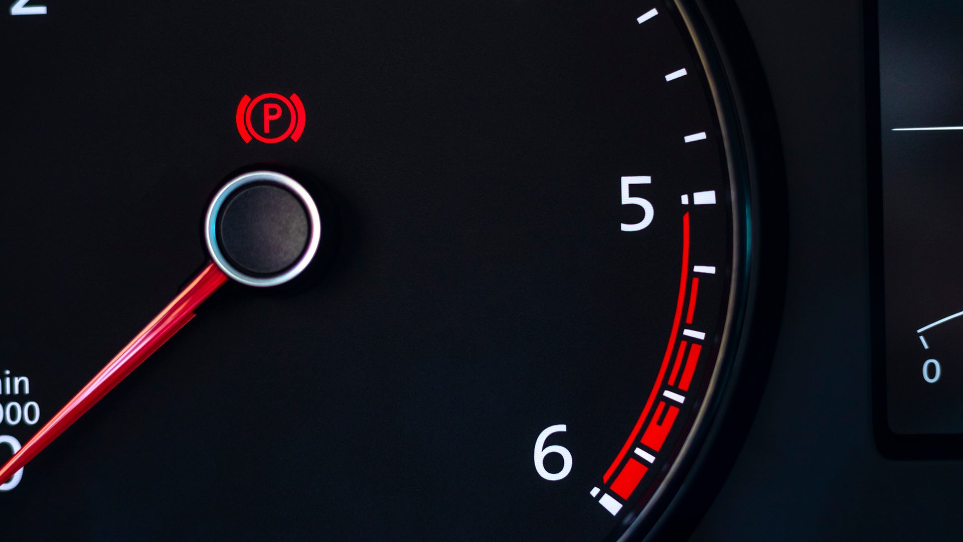 A car tachometer with the parking brake light on.