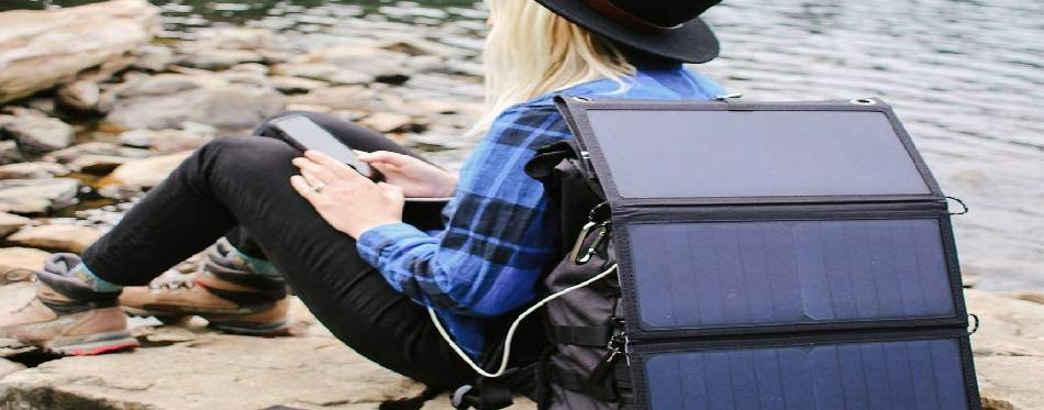 A hiker girl taking a rest while charging her smartphone with solar backpack charger