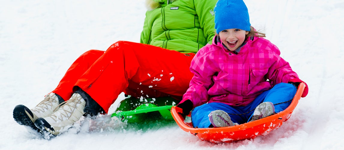 Family having fun at winter time using best sleds