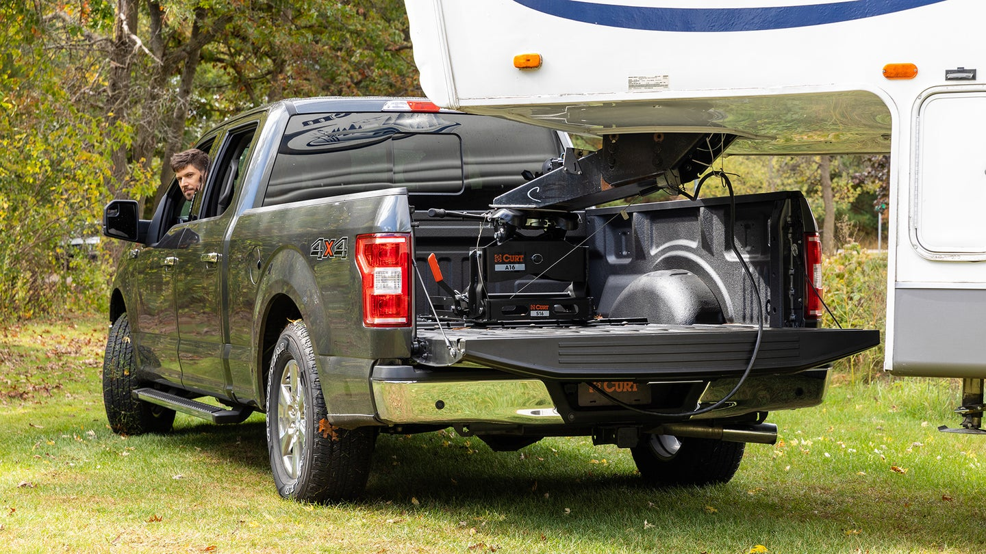 A fifth wheel trailer attached to a pickup truck.