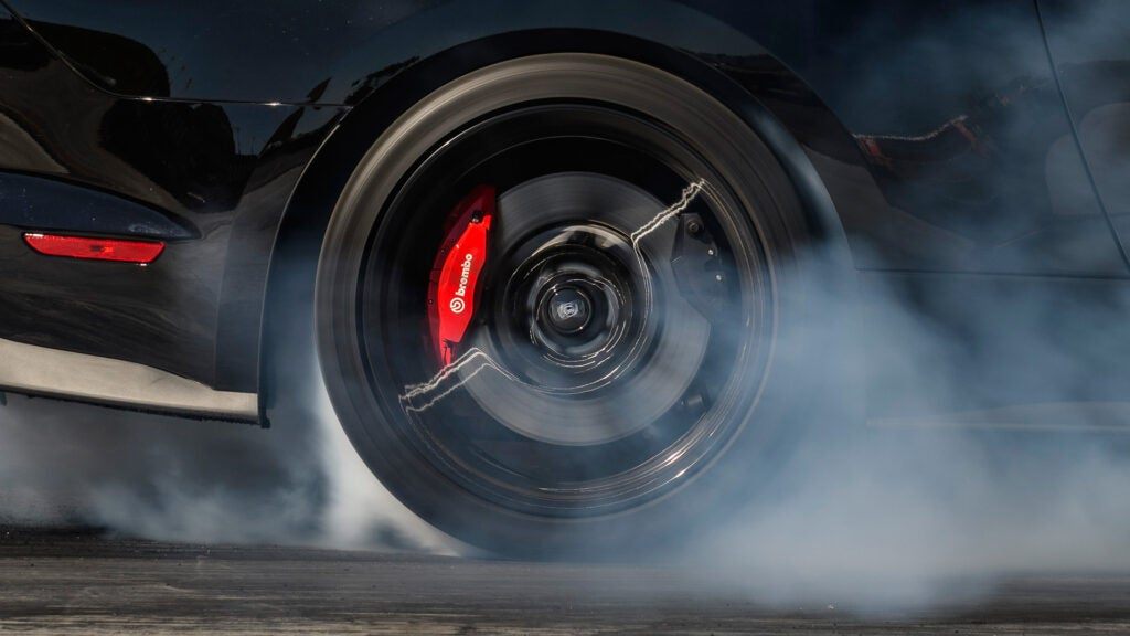 A Ford Mustang rear wheel with Brembo brakes doing a burnout.