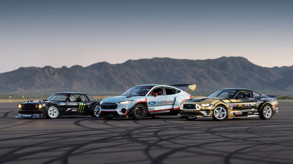 Ken Block's Hoonicorn next to a Mustang Mach-E and a racing Ford Mustang.