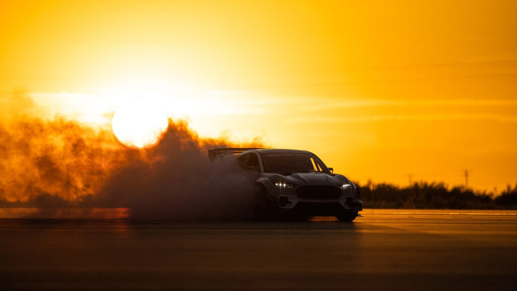 A Ford Mustang Mach-E drifts in a billow of smoke against an orange sunset.