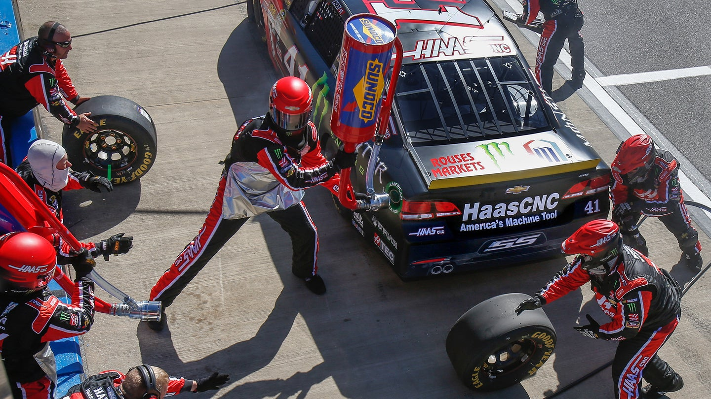 A member of the pit crew refills a NASCAR with Sunoco fuel.
