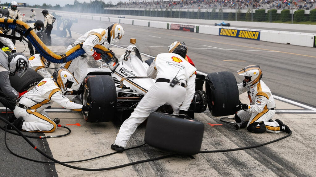 The pit crew puts new tires and fuel into an Indycar.