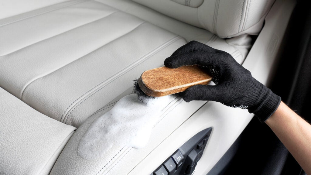 A gloved hand brushes and cleans a white leather driver's seat.