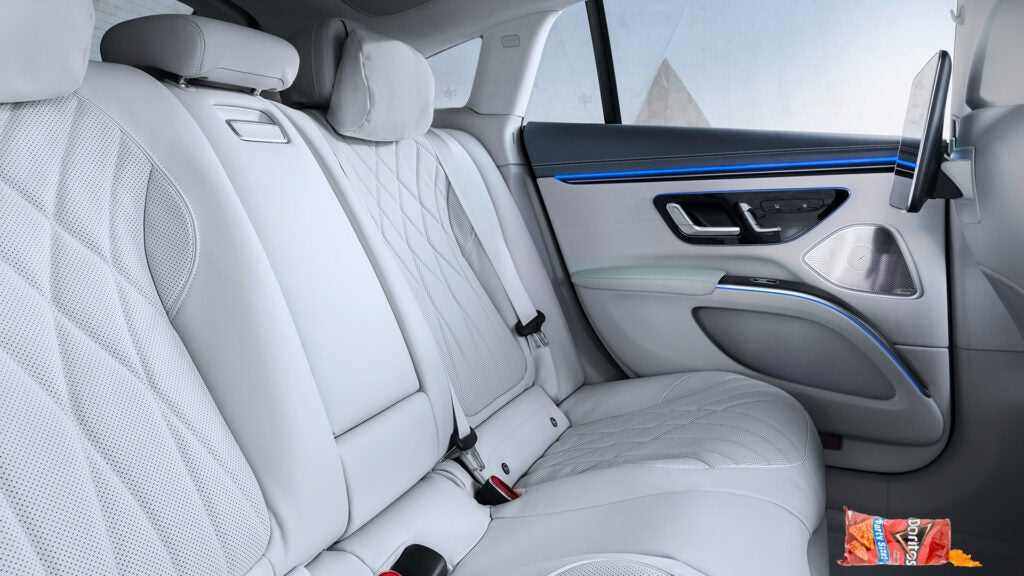 The white quilted backseat interior of a Mercedes-Benz EQS.
