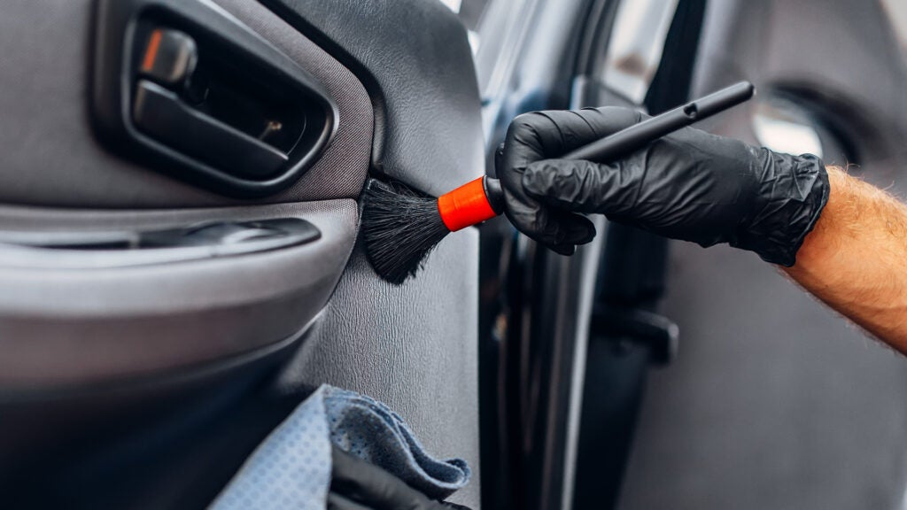 A gloved hand uses a detail brush to clean a door panel.