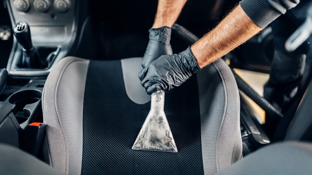 A man wet vacuuming a front seat of a car.