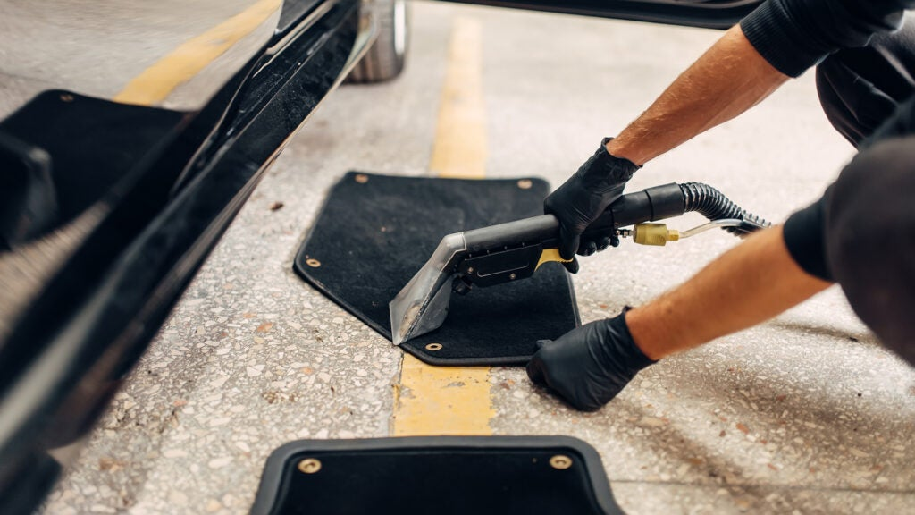 A detailer uses a vacuum to clean floor mats outside of the car.